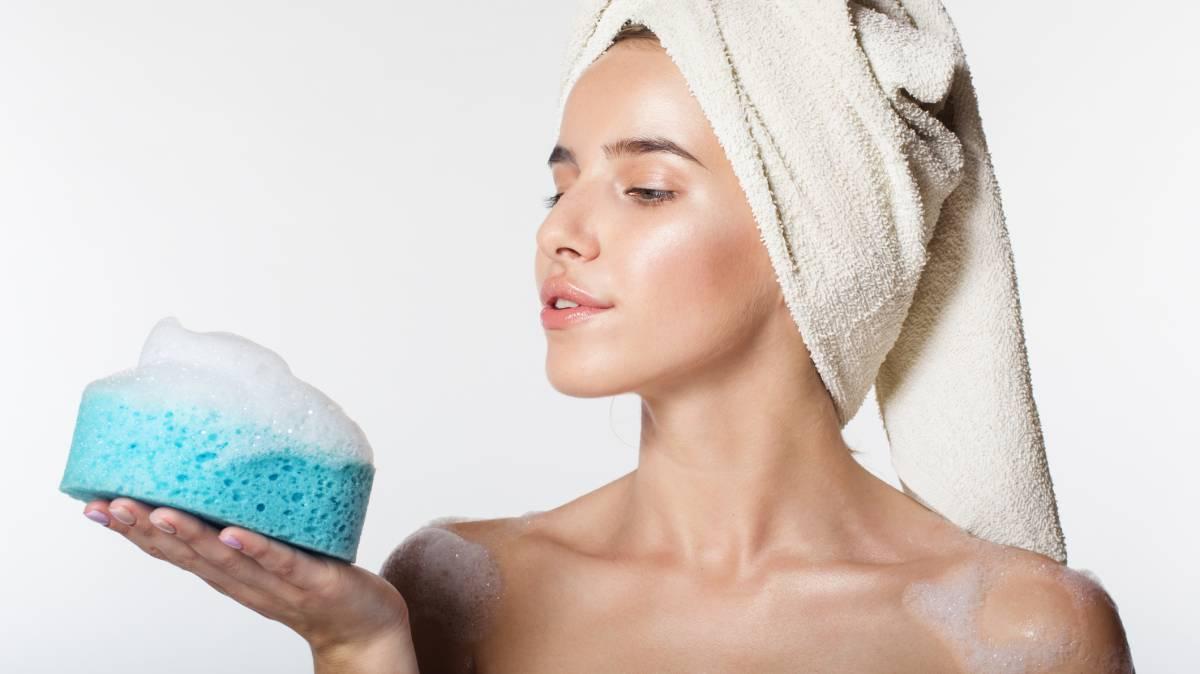 Mujer joven recién salida de la ducha, con toalla en la cabeza y mirando esponja con restos de jabón