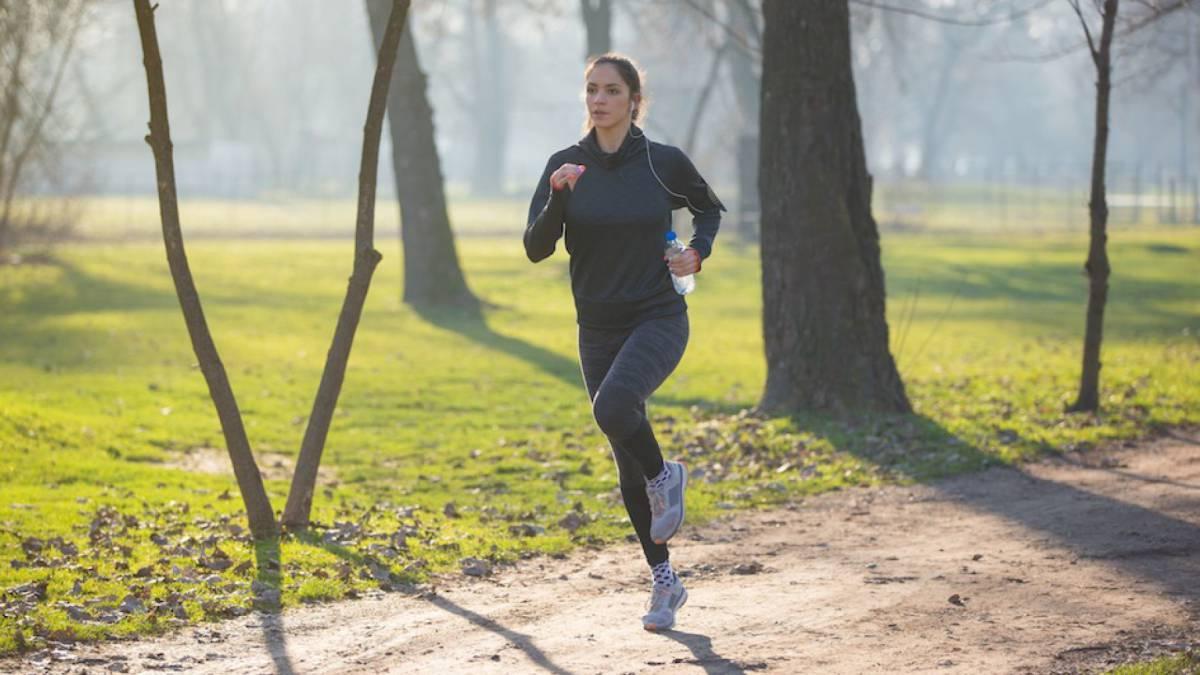 Chica haciendo running por un parque con frío