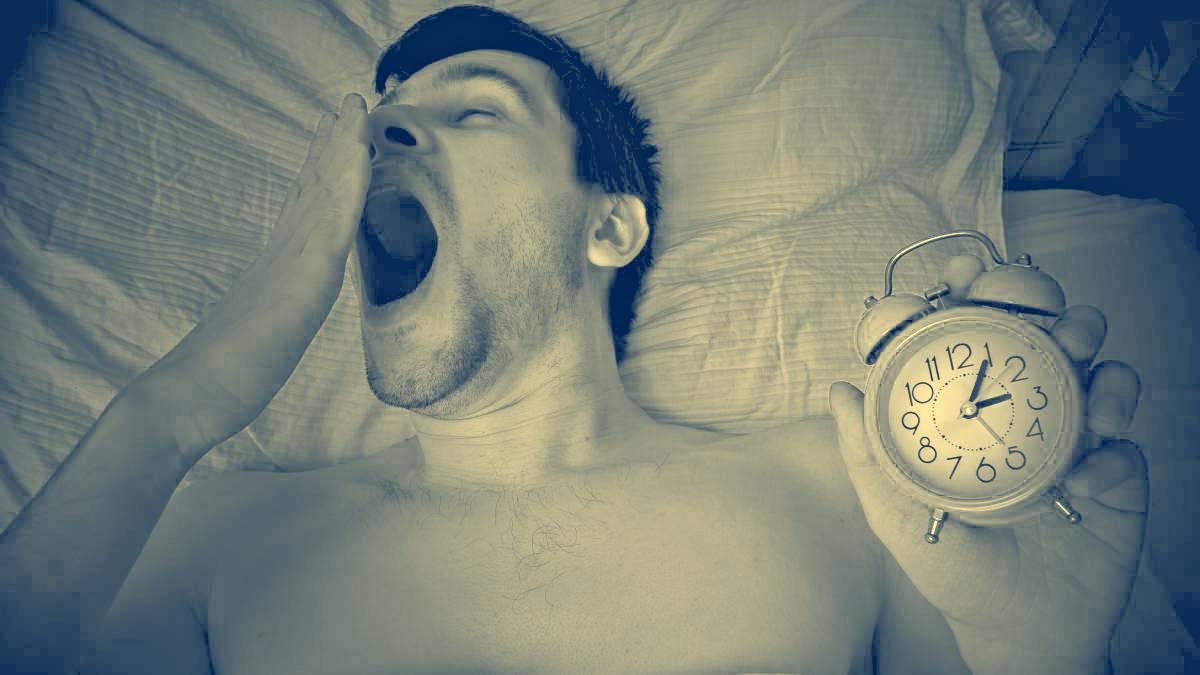 Hombre en la cama bostezando