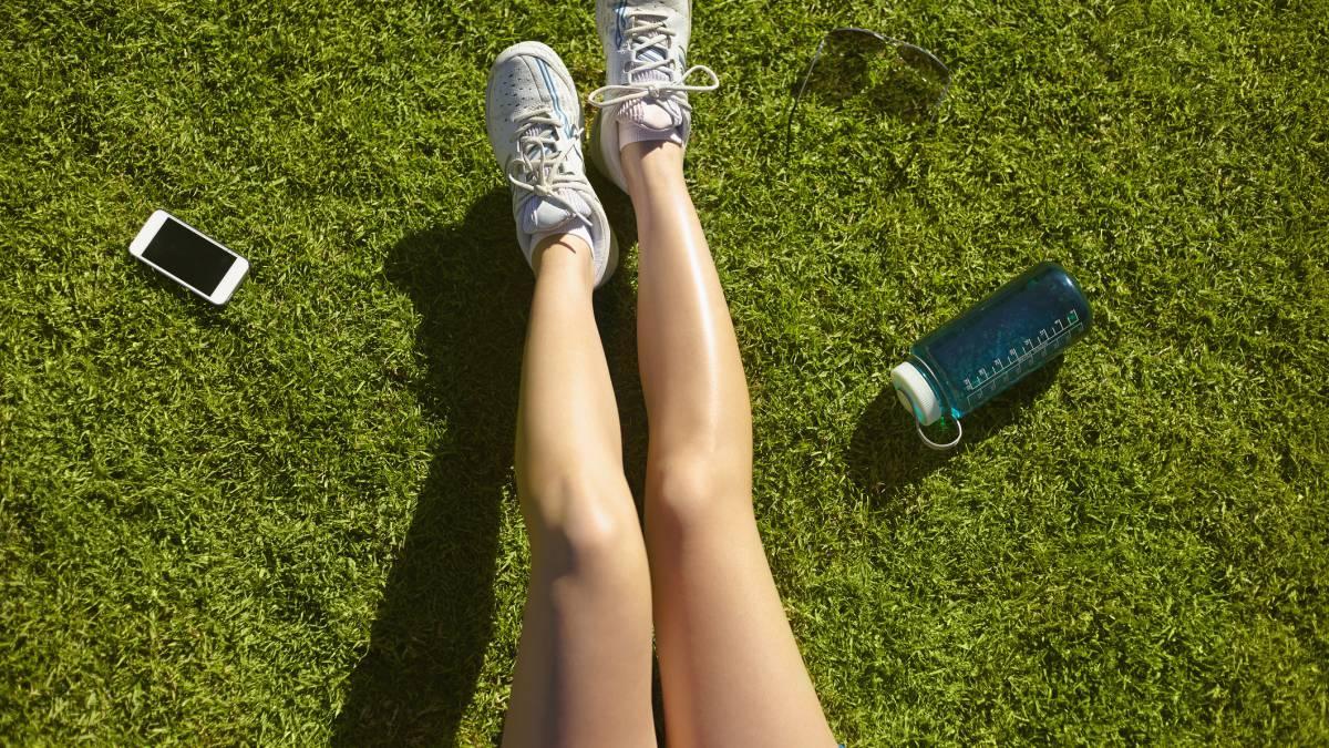 Piernas de mujer tumbada en el césped, llevando zapatillas de deporte
