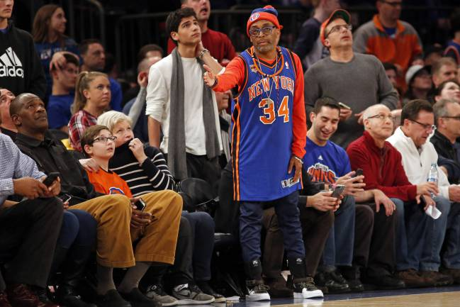 Wearing a Charles Oakley jersey director Spike Lee reacts during the second half against the San Antonio Spurs at Madison Square Garden