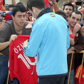 Cesc firma un autógrafo en una camiseta del Madrid