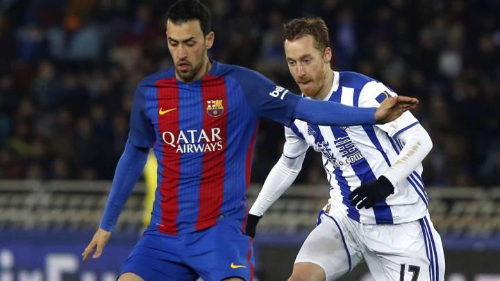 El centrocampista del F. C. Barcelona, Sergio Busquets, protege el balón ante el jugador de la Real Sociedad, David Zurutuza, durante el encuentro correspondiente a la ida de los cuartos de final de la Copa del Rey, que disputan esta noche en el estadio de Anoeta, en San Sebastián.