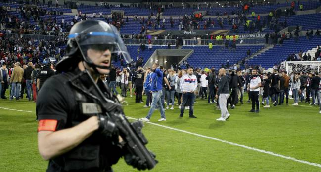 Police officers as Lyon fans invade the pitch and fans clash in the stands.