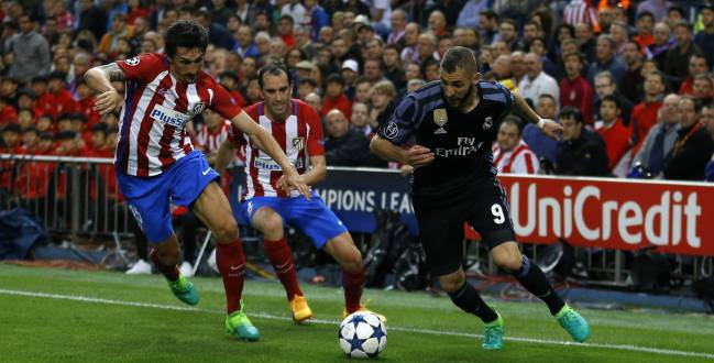 Real Madrid's Karim Benzema, right, controls the ball as Atletico Madrid's Stefan Savic, left, and Diego Godin try to stop him during the Champions League semifinal second leg soccer match between Atletico Madrid and Real Madrid at the Vicente Calderon stadium in Madrid, Wednesday, May 10, 2017.