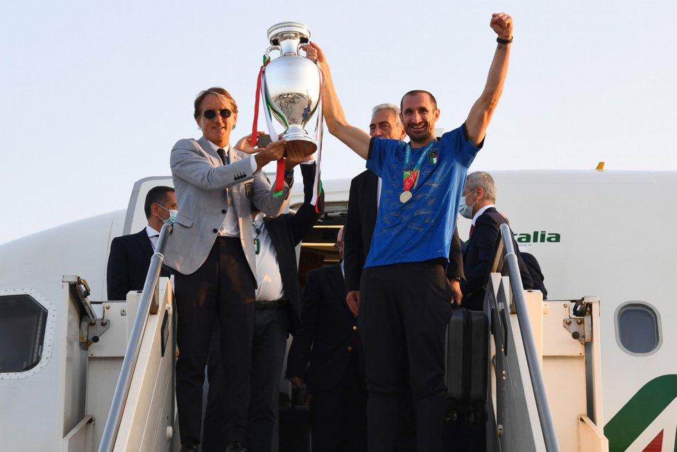 Roberto Mancini y Bonucci con la copa a la salida del avión.