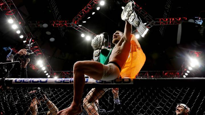 Conor McGregor luce sus dos cinturones mundiales tras ganar a Eddie Álvarez.