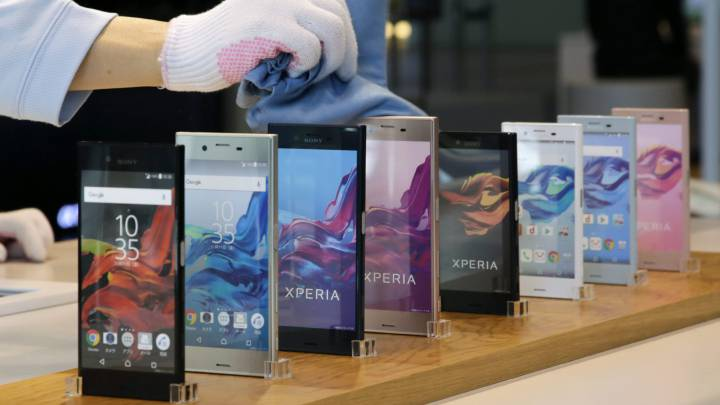 Un trabajador limpia unos móviles Xperia de la compañía Sony expuestos en su sede en Tokio (Japón).