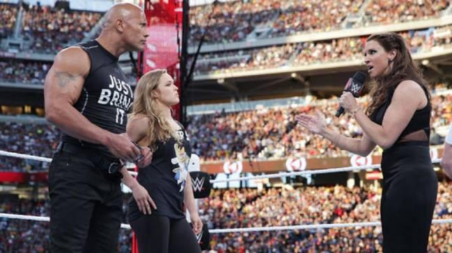 "Stephanie McMahon se dirige a Ronda Rousey y Dwayne ""The Rock"" Johnson durante el Wrestlemania 31."