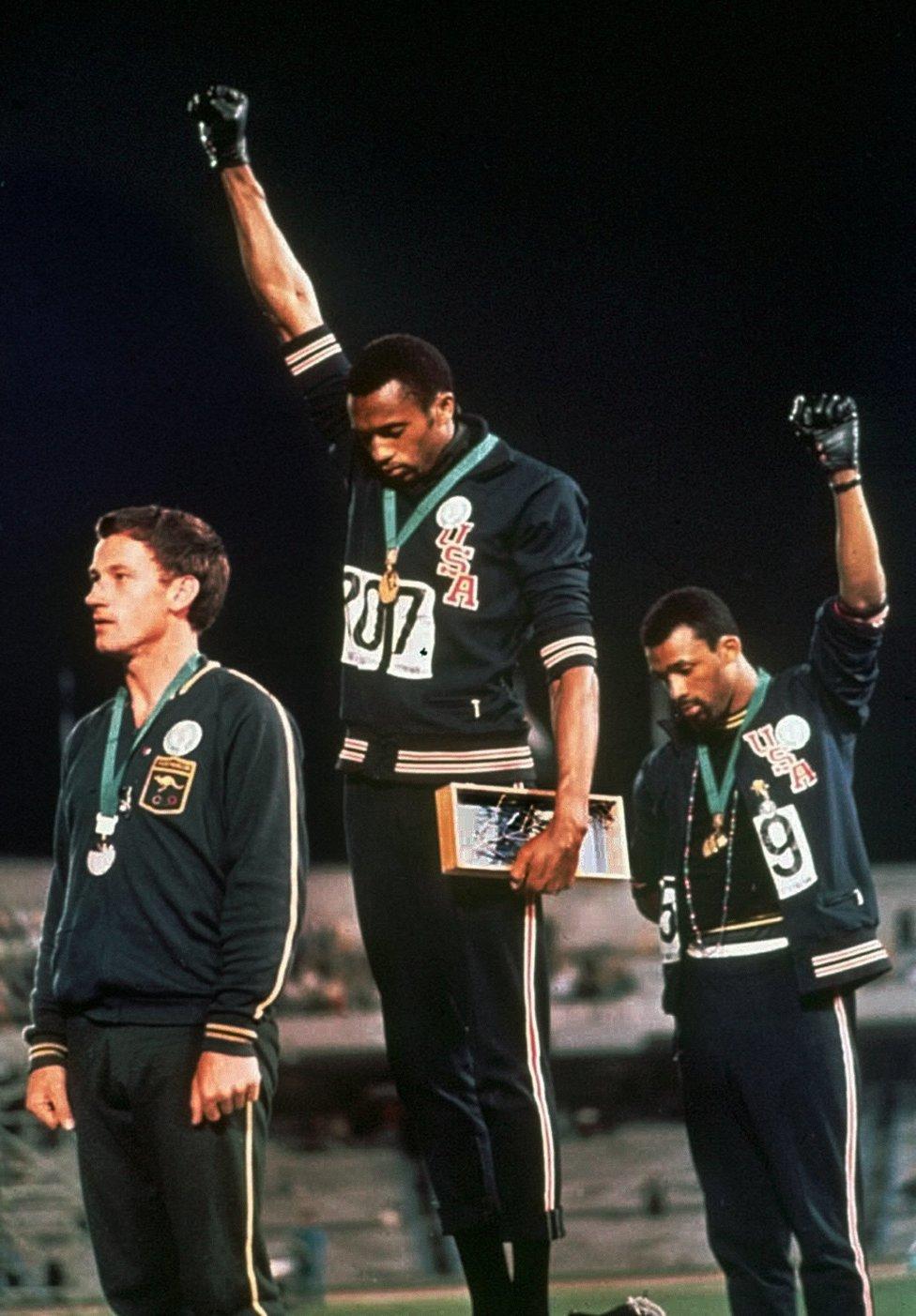 Tommie Smith (centro) y John Carlos (derecha) levantan sus puños con guantes negros en el pódium