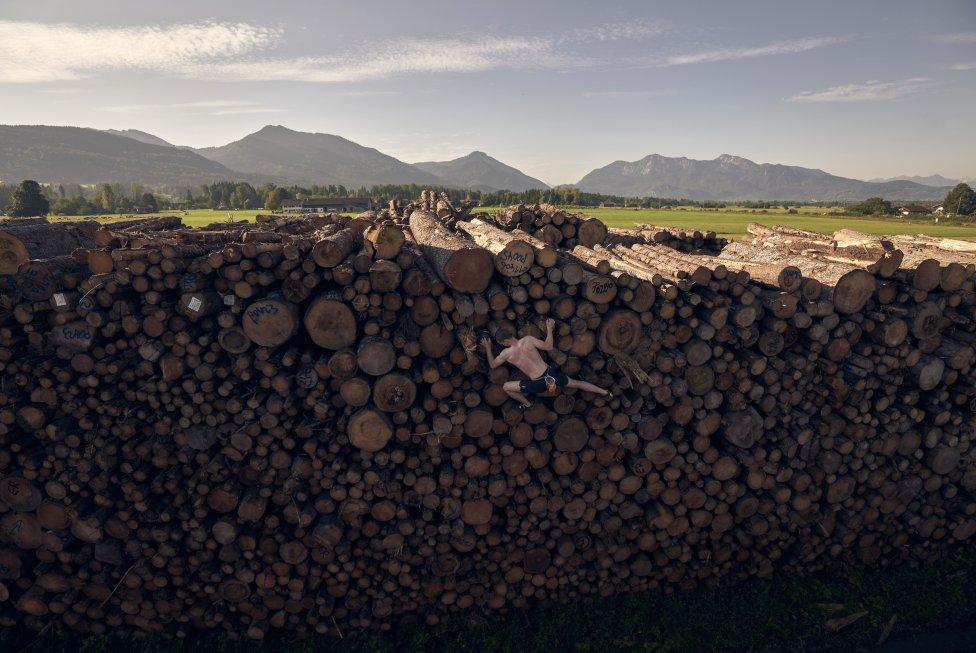 El alemán Georg Filser-Mayerhofer sube una pila de troncos mientras realiza un entrenamiento de búlder, una modalidad de escalada que consiste en escalar bloques de roca o pequeñas montañas que pueden ser de 8 metros, sin materiales de protección