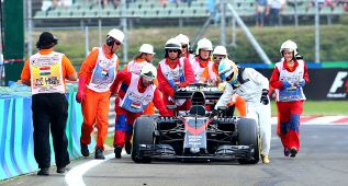 Alonso entró a boxes empujando su McLaren