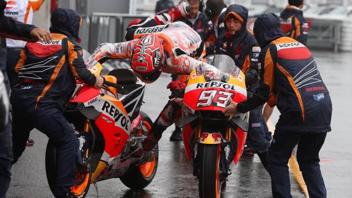 Mecánicos con casco para el cambio de moto en el pit lane