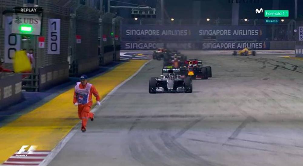 Un comisario esquiva a los coches de F1 en Singapur