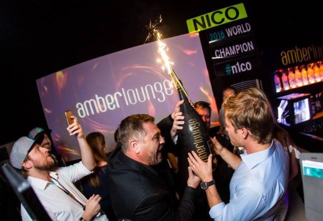 Rosberg agasajado con una botella de champán.
