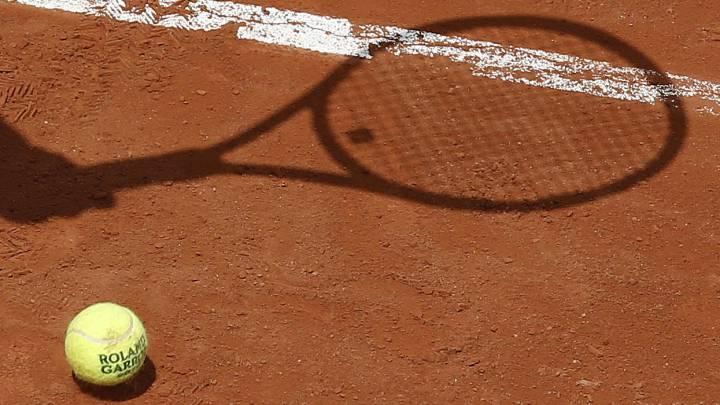 Sombra de una raqueta sobre una pista de tenis.