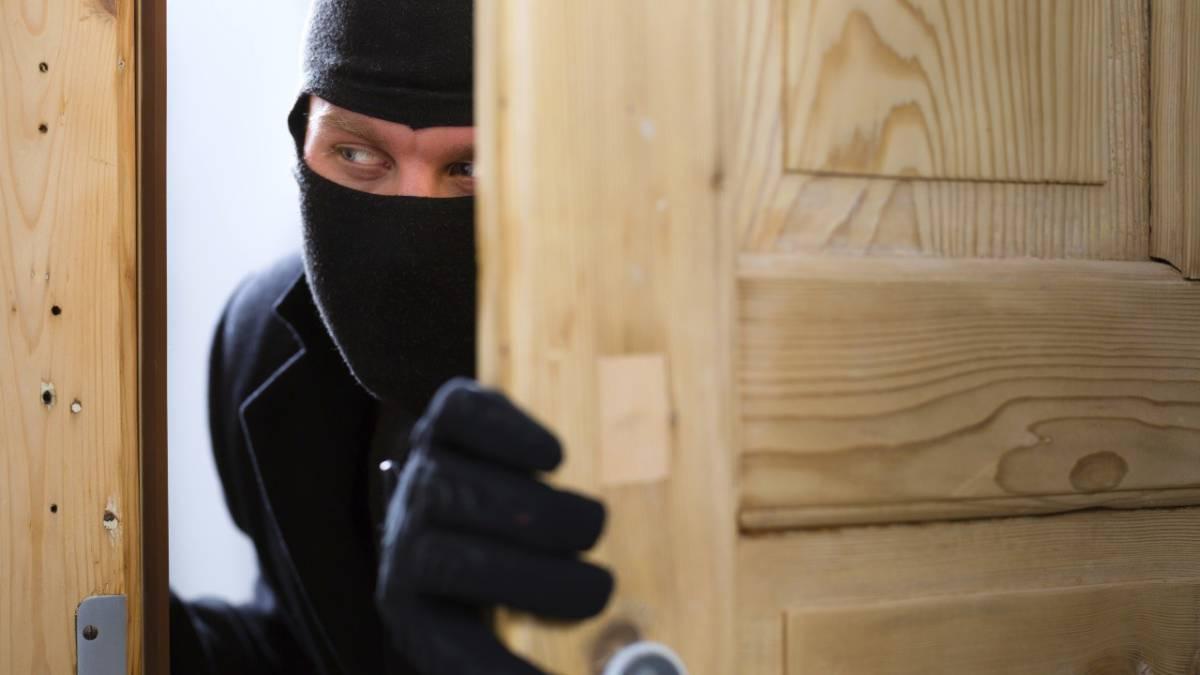 Un ladrón abre una puerta de una casa