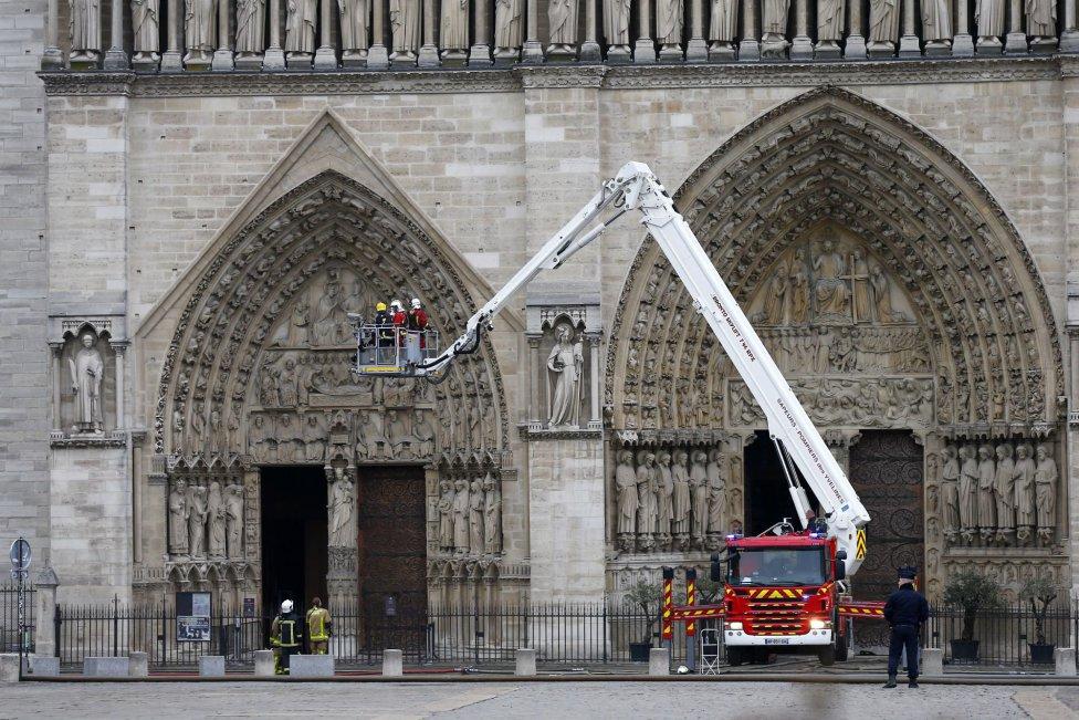 Varios bomberos trabajan en un elevador a la fachada de catedral de Notre Dame