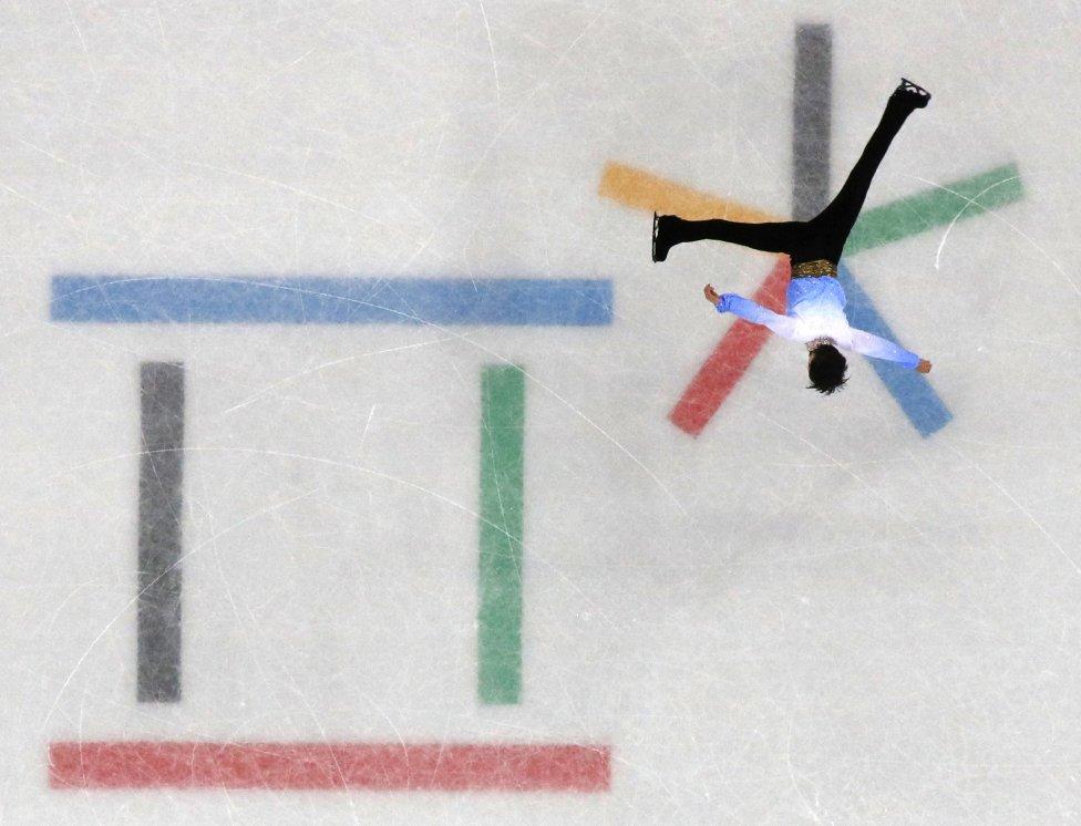 En esta imagen parece que el patinador japonés Yuzuru Hanyu formara parate del logotipo de los Juegos Olímpicos que hay pintado en el hielo de la pista.