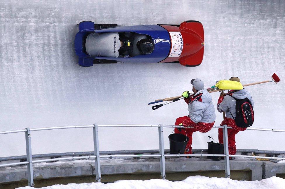 Estos operarios de la pista de bobsleigh tienen una posición privilegiada durante la prueba, aunque no lo parezca están trabajando.