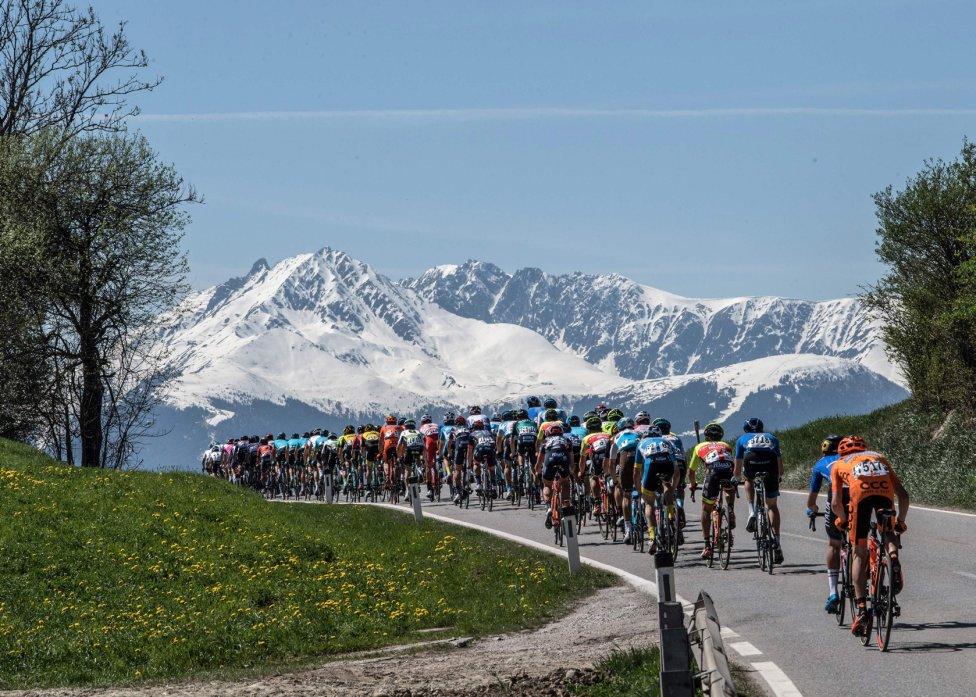 Camino a la nieve. Este pelotón ciclista rueda por una carretera camino de los Alpes, con las montañas llenas de nieve.