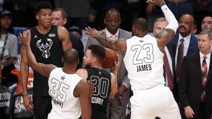 Kevin Durant y Stephen Curry impiden lanzar a Stephen Curry en la última posesión del All Star Game de la NBA 2018.