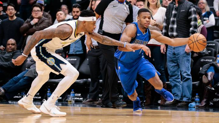 Dennis Smith Jr. ante la defensa de Torrey Craig.