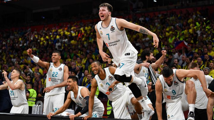 Real Madrid's Slovenian Luka Doncic (C-7) jumps over the barrier as the team celebrates their 85-80 win in the Euroleague Final Four finals basketball match between Real Madrid and Fenerbahce Dogus Istanbul at The Stark Arena in Belgrade on May 20, 2018. / AFP PHOTO / Andrej ISAKOVIC