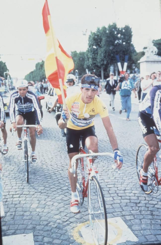 Perico Delgado, campeón del Tour de Francia en 1988, con la bandera de España y vestido de amarillo por los Campos Elíseos.
