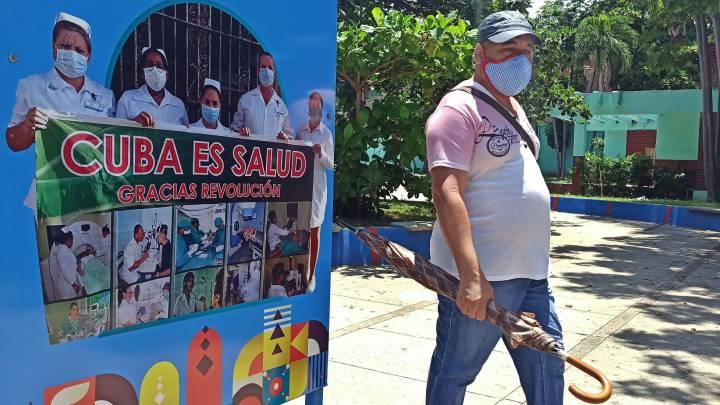 Un hombre con mascarilla pasa junto a un cartel que promociona logros en salud debidos a la revolución, hoy en La Habana (Cuba).