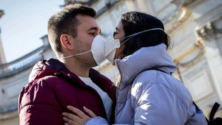 Imagen de una pareja besándose con mascarilla.