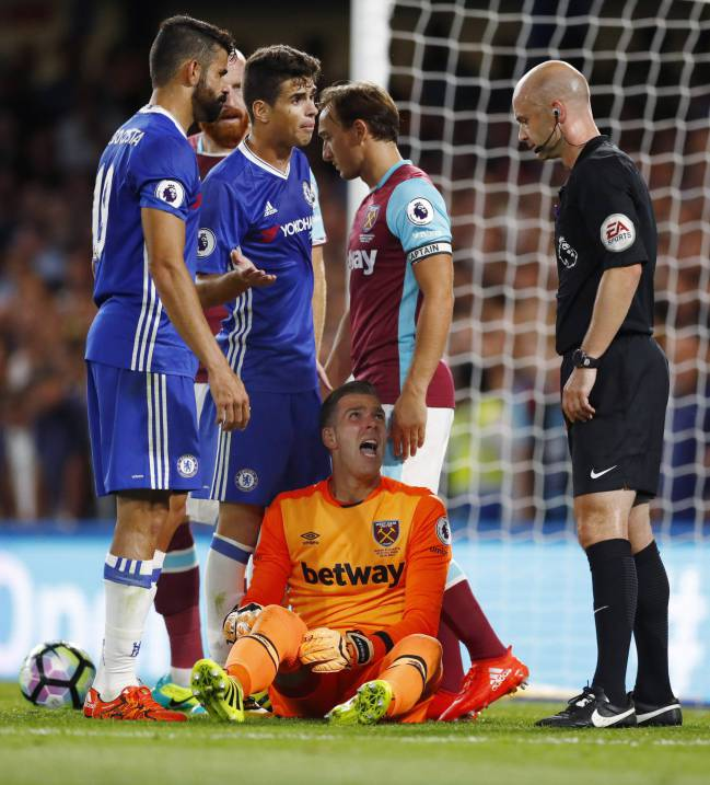 Referee Anthony Taylor looks on as West Ham's Adrian reacts after a tackle with Chelsea's Diego Costa