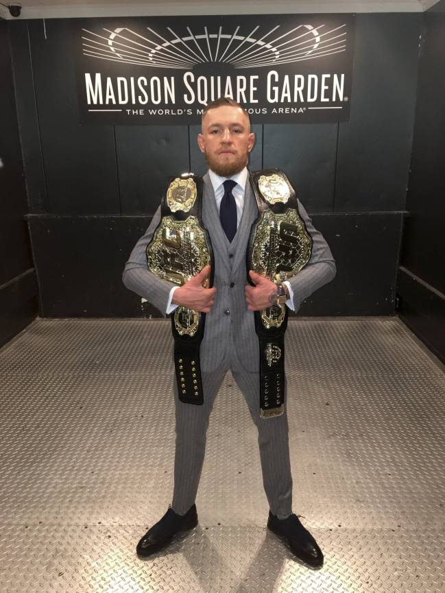 Conor McGregor with his two belts.