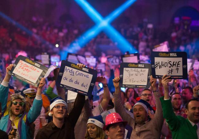 Fans hold up messages ahead of the PDC World Championship darts final between Netherlands' Michael van Gerwen and Scotland's Gary Anderson
