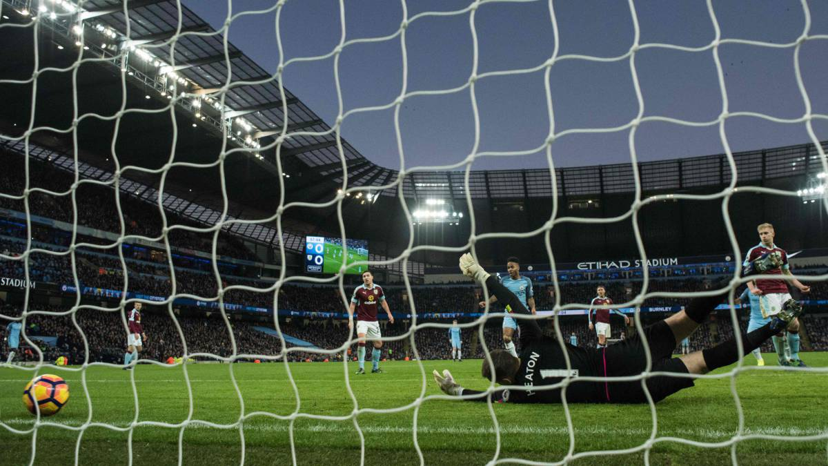 Burnley's English goalkeeper Tom Heaton dives but fails to save a shot from Manchester City's French defender Gael Clichy