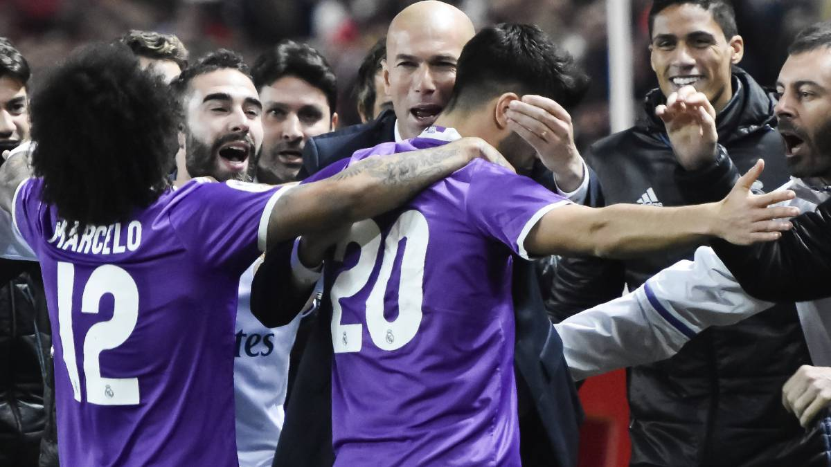 Real Madrid's Marco Asensio celebrates with players and manager.