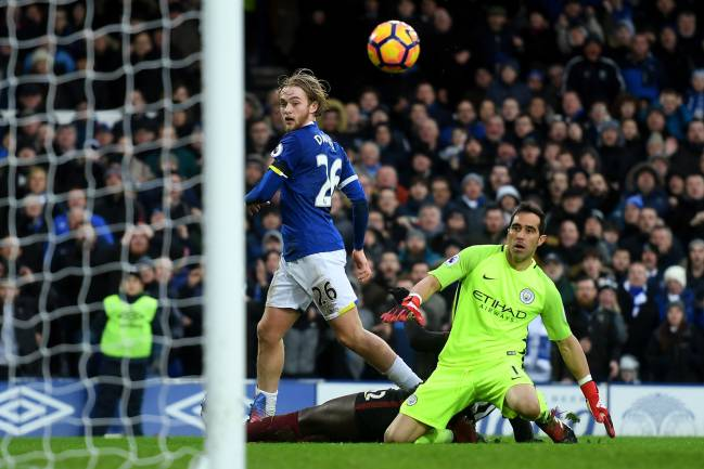 Tom Davies of Everton lifts the ball over goalkeeper Claudio Bravo of Manchester City