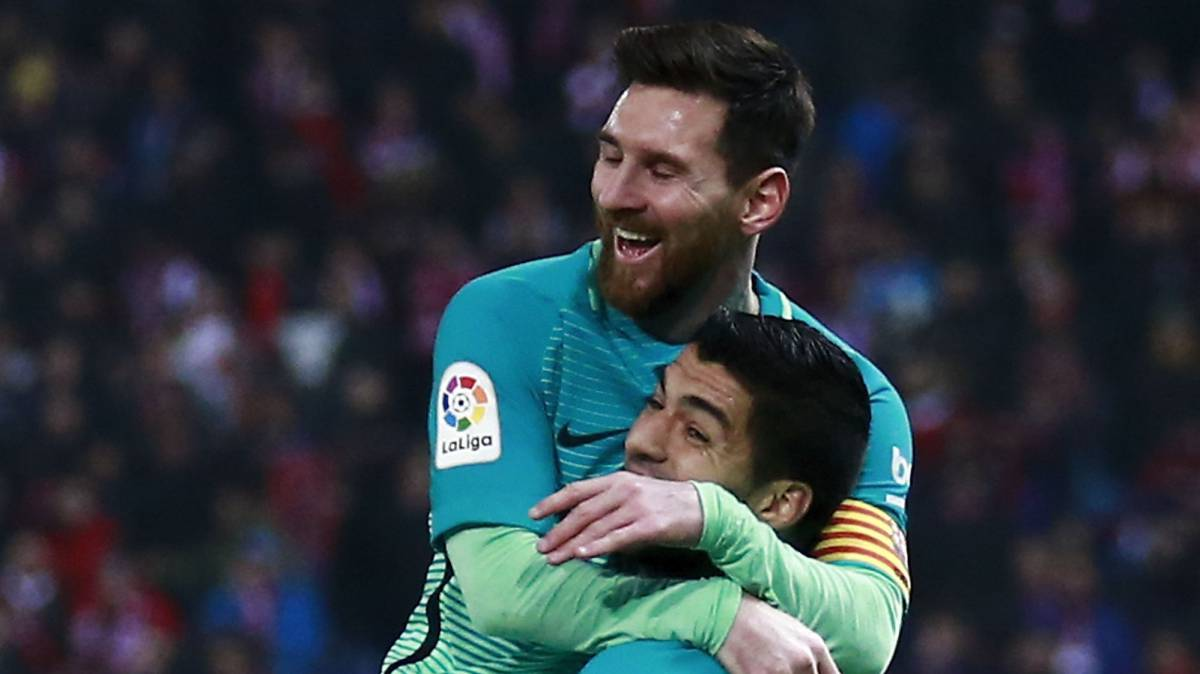 Lionel Messi (L) of FC Barcelona celebrates scoring their second goal with teammates Luis Suarez (R) a during the Copa del Rey semi-final first leg match between Club Atletico de Madrid and Barcelona