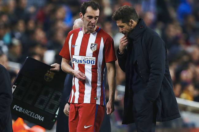 Diego Godin informs Diego Simeone of his injury after being subbed against Barcelona.