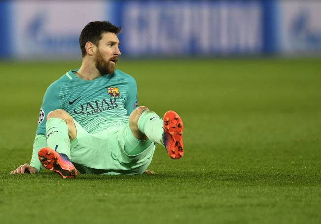 Messi sits during the UEFA Champions League round of 16 first leg football match between Paris Saint-Germain and FC Barcelona