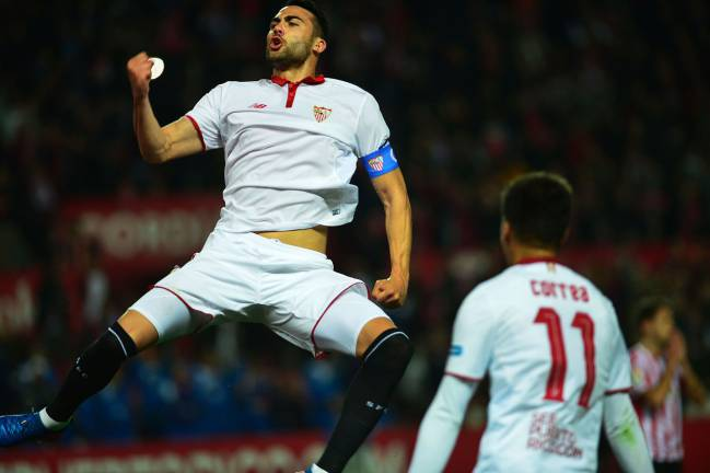Sevilla's midfielder Vicente Iborra celebrates after scoring the penalty rebound.