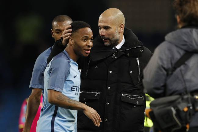Manchester City manager Pep Guardiola celebrates with Raheem Sterling.