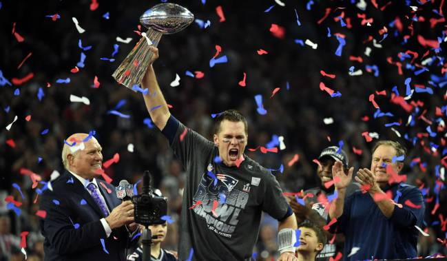 Tom Brady of the New England Patriots holding the Vince Lombardi Trophy as Head coach Bill Belichick looks on