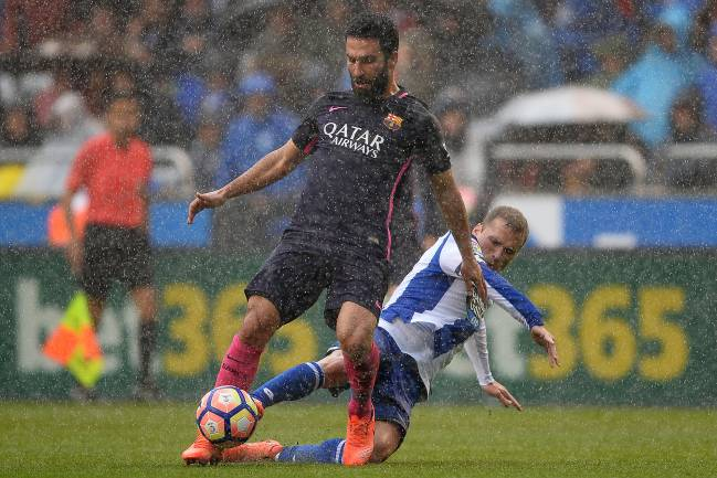 Alex Bergantinos of RC Deportivo La Coruna competes for the ball with Arda Turan of FC Barcelona