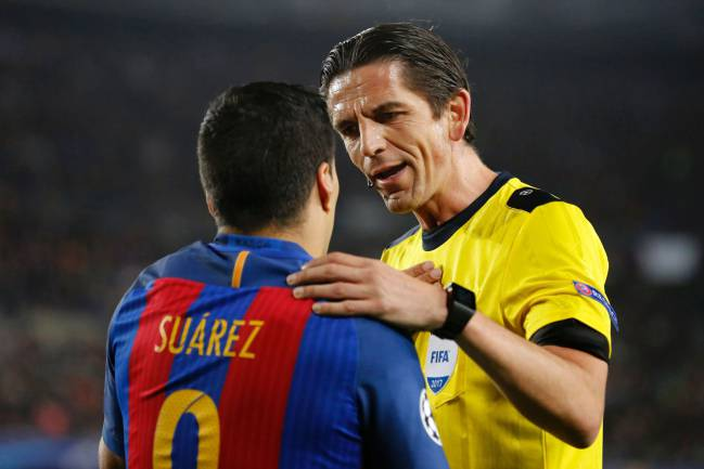 Referee puts hand on shoulder of Barcelona's Uruguayan forward Luis Suarez