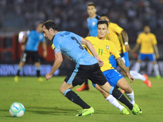 Uruguay's Diego Godin vies for the ball with Brazil's midfielder Philippe Coutinho.