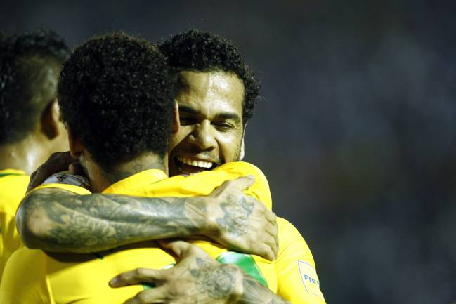 Brazil's Neymar given a big hug by Dani Alves after his goal gave a comfortable lead over Uruguay.
