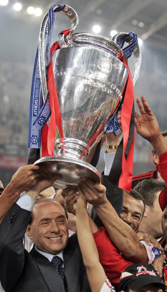 Athens May 23, 2007 | AC Milan's Silvio Berlusconi raises the trophy aloft as he stands with his team after they beat Liverpool 2-1 to win the Champions League.