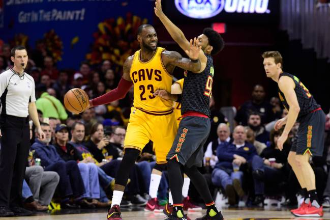 LeBron James of the Cleveland Cavaliers looks for a pass while under pressure from DeAndre' Bembry