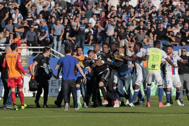 Lyon's goalkeeper Anthony Lopes attacked by Bastia supporters who invaded the pitch at the Armand Cesari stadium.